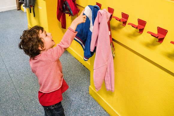 Lapsi päiväkodissa, osoittaa sormellaan jotain ylhäällä seinällä olevaa asiaa.