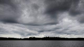 tummia pilviä taivaalla ja harmaa meri