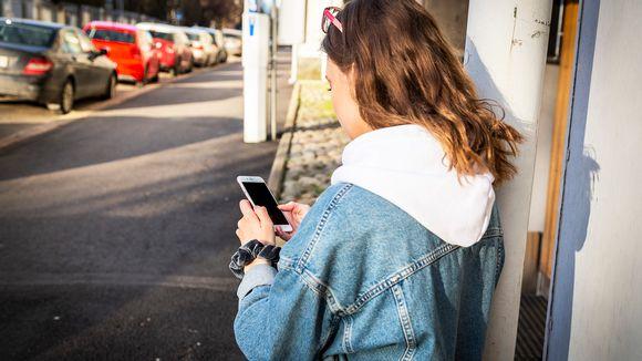 nuori nainen käyttää kännykkää