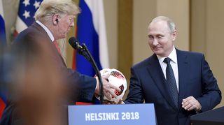 Vladimir Putin ojentaa jalkapallon Donald Trumpille tiedotustilaisuudessa Helsingissä.