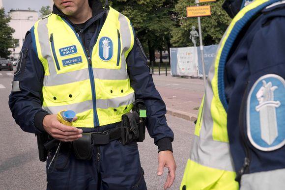 Poliisi kädessään alkometri.