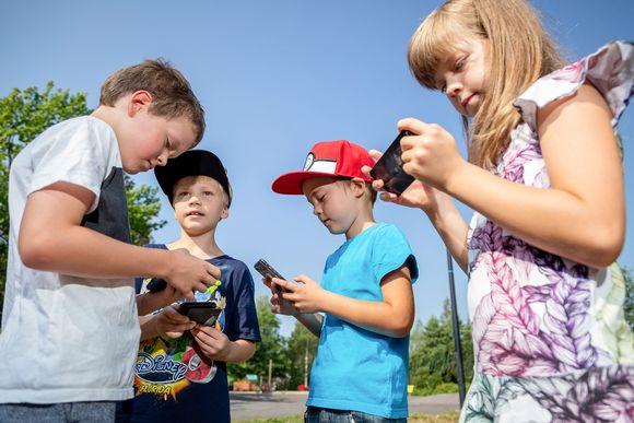 Neljä lasta tutkivat kännyköitään