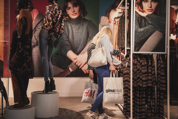 Kaksi nuorta naista katselee vaatteita kaupassa.