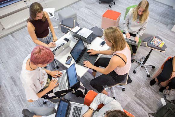 viisi opiskelijaa työskentelee tietokoneella. Viikin normaalikoulun lukiolaisilla läppärit ovat ahkerassa käytössä melkein joka tunnilla.