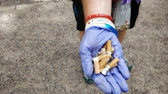Tupakantumppeja kädessä.