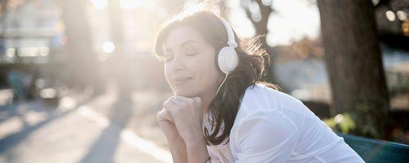nainen kuuntelee kuulokkeilla