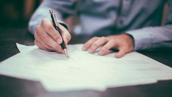 Henkilö allekirjoittaa työsopimusta.