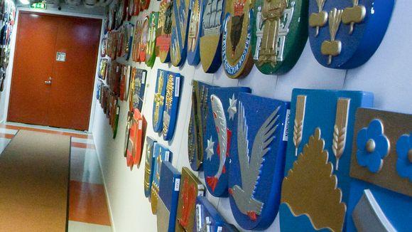 Kuntavaakunoita käytävän seinillä.