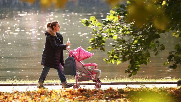Nainen työntää lastenvaunuja puistossa.