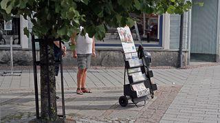 Jehovan todistajia lehtitelineen vieressä.