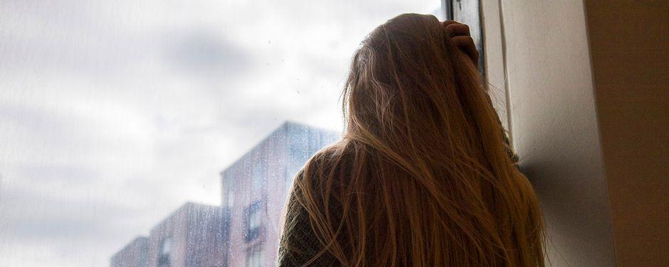 nainen katsoo ikkunasta