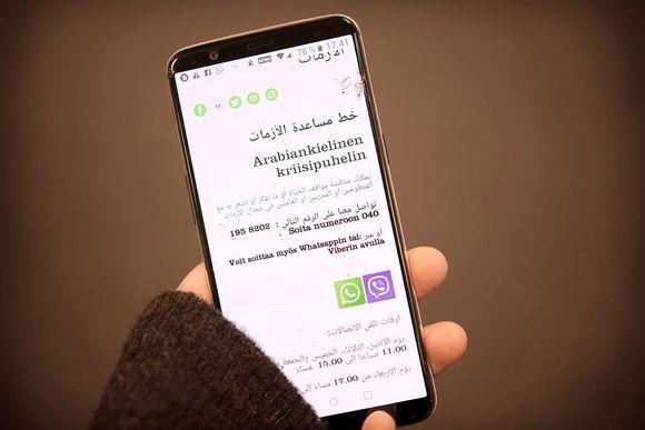 Arabiankielisen kriisipuhelimen verkkosivu puhelimen näytöllä.