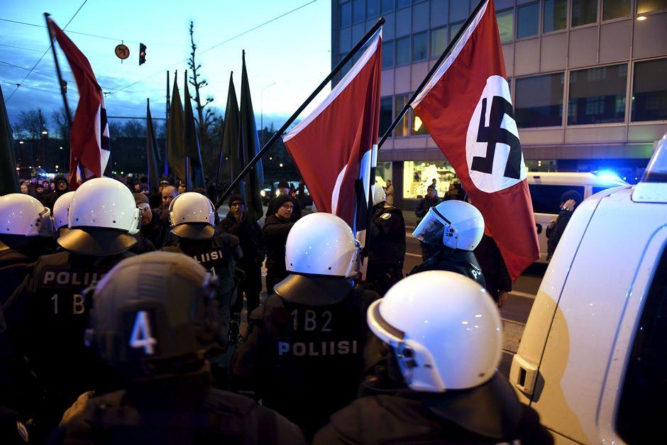 Poliisit poistivat hakaristiliput mielenosoittajilta.