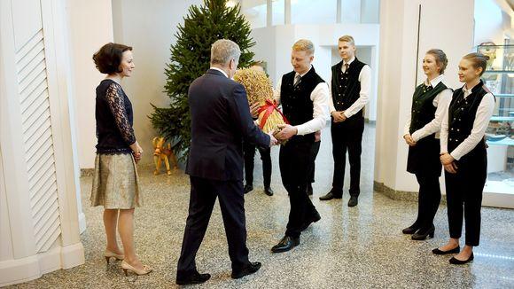 Sauli Niinistö ja Jenni Haukio vastaanottavat metsäylioppilaiden lahjoittaman joulukuusen presidentin virka-asunnolla.