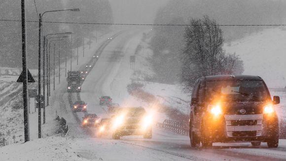 Autoja maantiellä lumisateessa.