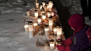 Muistokynttilöitä lumella.