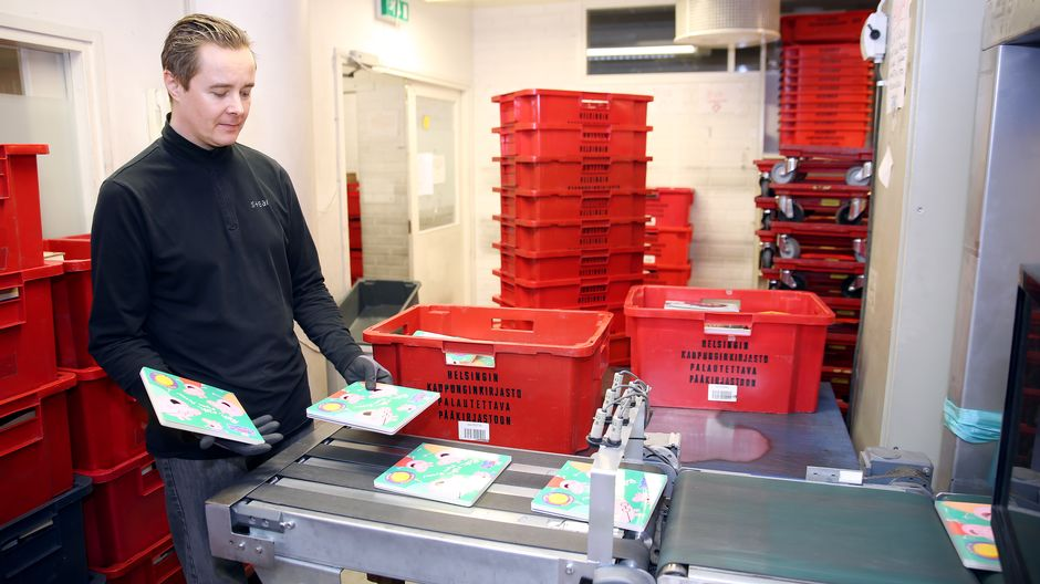 Virkailija käsittelee palautettuja kirjoja hihnalla Helsingin kaupunginkirjaston logistiikkayksikössä Pasilassa.