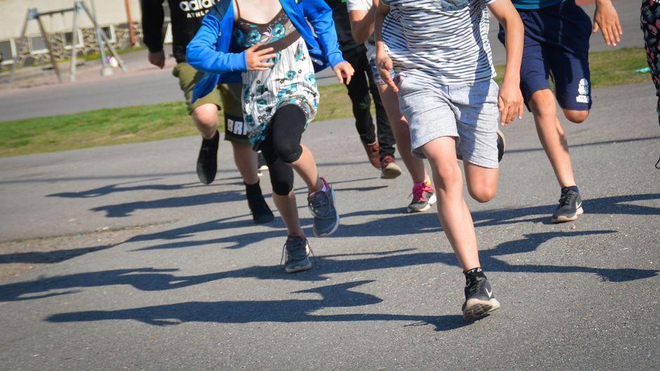 Koululaisia juoksee ulkona