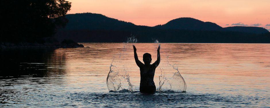 uimarin silhuetti kesäillassa