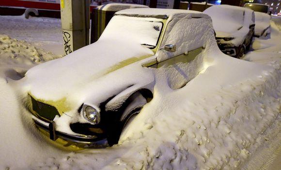 Lumisia autoja jääneet lumivallin taakse aurauksen jäljiltä.