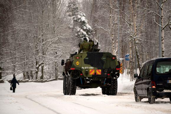 Puolustusvoimien sotilaita sotilasajoneuvon kyydissä lumisessa katumaisemassa.