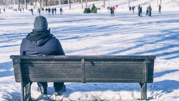 yksinäinen mies penkillä, taustalla luistelijoita