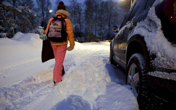 tyttö kävelee lumihangessa tiellä