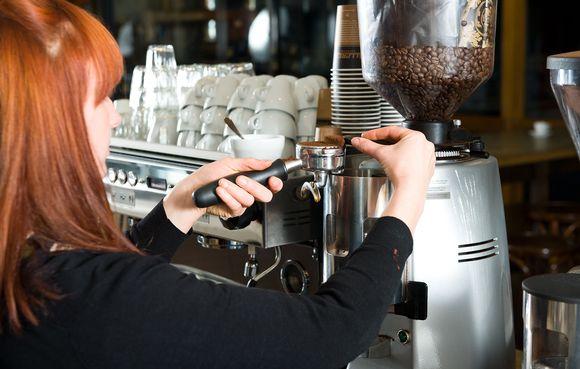 nuori punatukkainen nainen täyttää kahvilaitetta