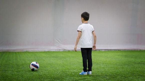 lapsi pelaamassa jalkapalloa