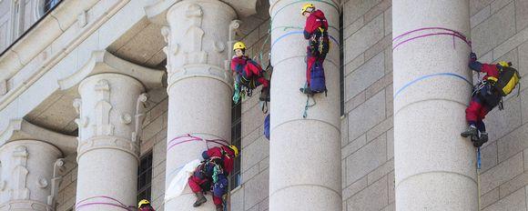 Eduskuntatalon pylväisiin kiipesi vajaat kymmenen ihmistä, jotka olivat pukeutuneet ympäristöjärjestö Greenpeacen haalareihin Helsingissä 6.maaliskuuta