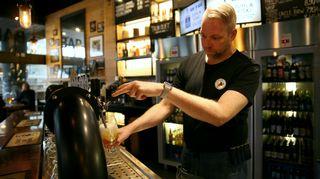 Kampin Teerenpelin ravintolapäällikkö Miika Korpela kaataa olutta hanasta.