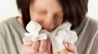 nainen aivastaa nenäliinaan