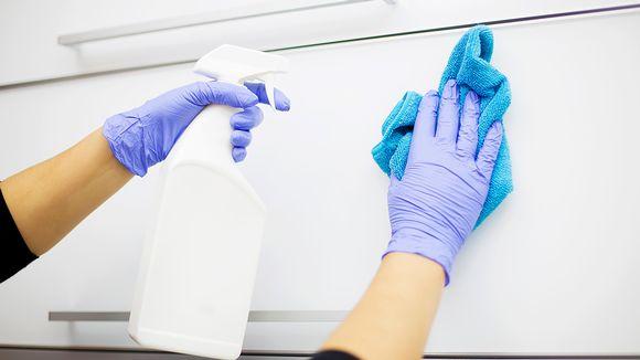 Siivoaja pesee kaapin ovia