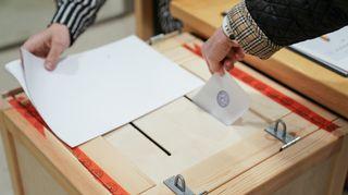 Henkilö tiputtaa äänestyslipukkeen vaaliuurnaan.