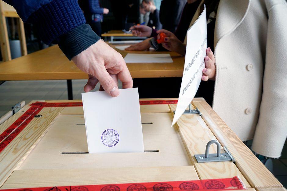 Äänestäjä tiputtaa äänestyslapun vaaliuurnaan.