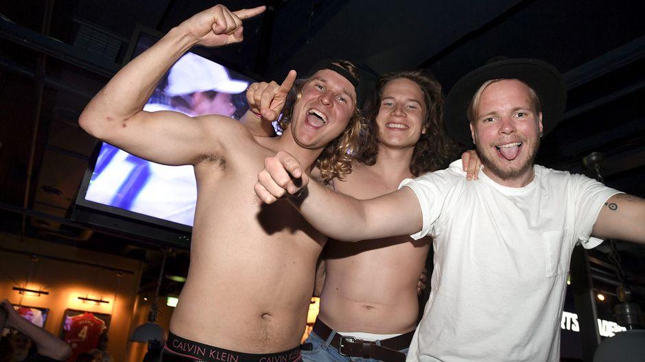 Suomalaiset juhlivat Suomen maailmanmestaruutta jääkiekosta Helsinkiläisessä baarissa.