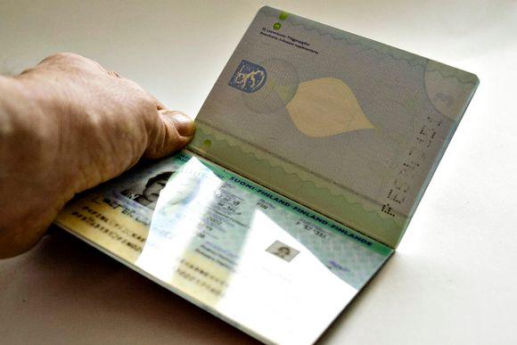 Suomen passi henkilön kädessä.