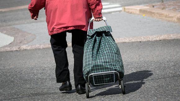 Iäkäs nainen vetää pyörällistä laukkua perässään.