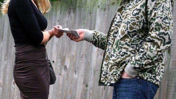 Mies ojentaa rahaa naiselle.