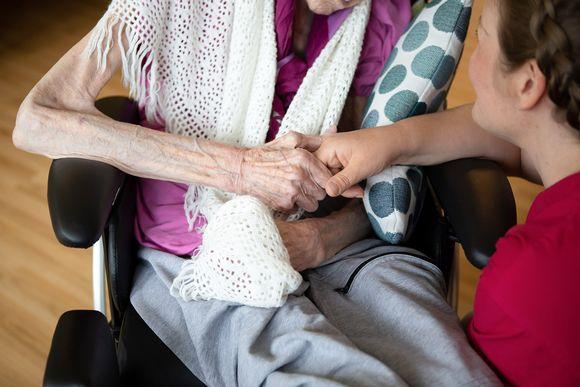 Lähihoitaja pitelee potilaan käsistä
