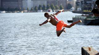 Uimari hyppää mereen Kalasatamassa Helsingissä 20. heinäkuuta.