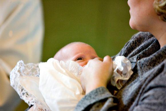 Vauva kastemekko päällään kummin sylissä.