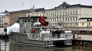 Harmaa kaksiponttooninen alus, taustalla kivirakennuksia, joista yksi Presidentinlinna.
