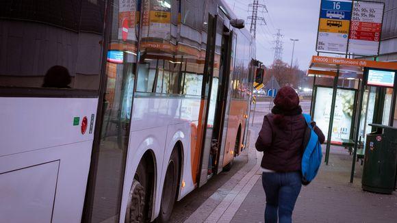 Nainen juoksee busiin.