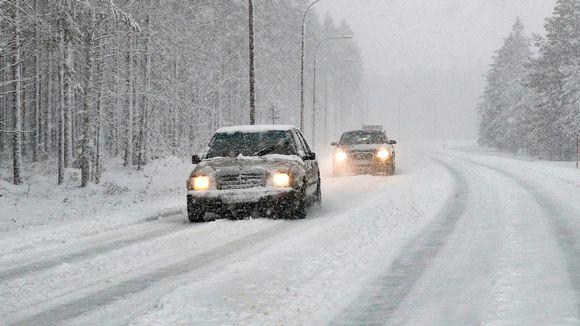 Autoja, liikennettä lumisateella.