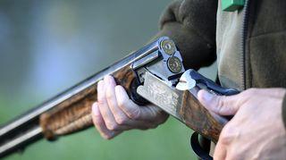 Metsästäjä käsitttelee asettaan.