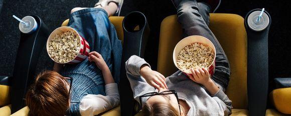 kaksi lasta katsoo elokuvaa teatterissa
