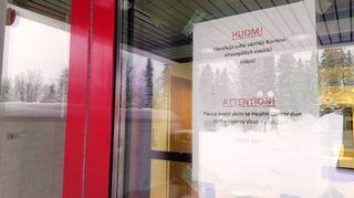 Varoituslappu Ivalon terveyskeskuksen ovessa.