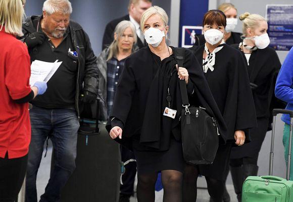Terveydenhoitohenkilökuntaa ja Punaisen Ristin työntekijöitä Helsinki-Vantaa lentokentällä vastaanottamassa Suomeen palaavia matkustajia 27. maaliskuuta.
