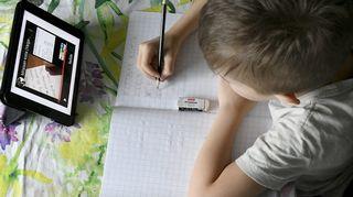 kaluokkalainen tekee koulutehtäviä etänä kotonaan Espoossa.